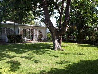 1 BR cottage style end unit set in tropical gardens, minutes walk to beach