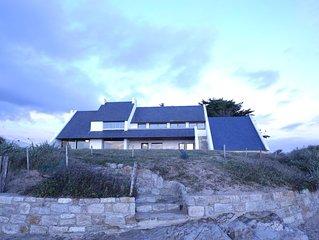 Grande maison surplombant la plage avec vue à 180° sur l'océan.