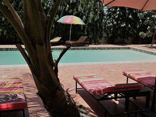 Room with kingbed and private bathroom in bed and breakfast with large pool.