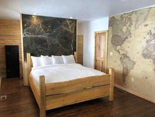 Master bedroom with log walls and a marble bed headboard and en-suite bathroom.