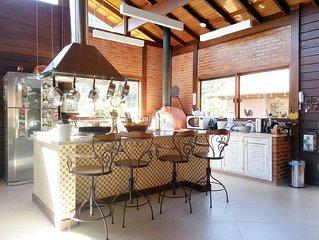 Casa aconchegante com piscina, hidromassagem, lareira, forno de pizza, jardim.