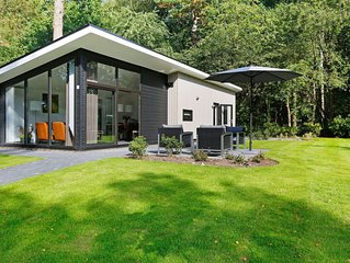 Modern designed chalet with a smart TV, next to the forest