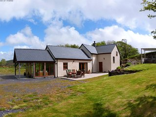 Drive up a single-track road to a tastefully renovated Denbigh farmhouse with sp