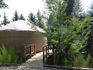 1 yourte contemporaine tout confort située dans un bois en terrasse avec vue.
