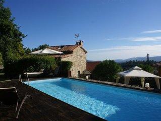 Casa de piedra con piscina y jardín.