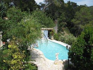 Mas provençal en pierres naturelles dans une colline boisée avec piscine .