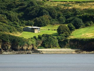 Cedar lodge in secluded location beside a beach in its own valley with far reach