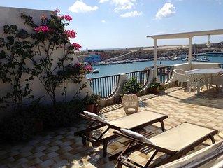 Lampedusa. Splendido grande attico con terrazzo fiorito sul  Porto delle Palme