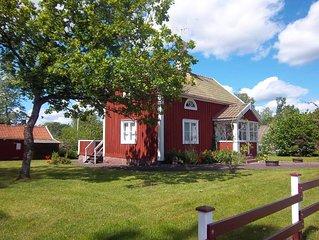 Rotes Holzhaus nähe See und Golfplatz mit Boot