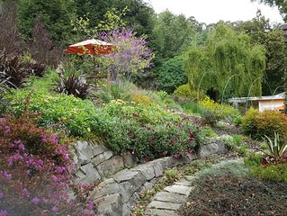 A cozy creekside cottage in a beautiful edible garden setting