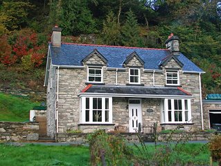 A classic Welsh period property with exposed stonework and a wood burner stove,