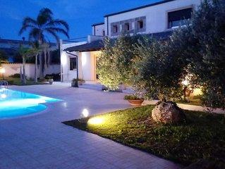 Moderna villa con giardino e piscina privata poco distante dal mare.