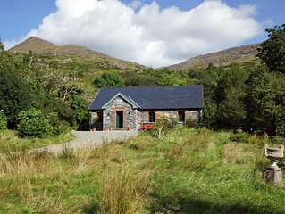 Detached stone faced cottage beside a stream and waterfalls on the slopes of the