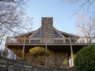 Stunning rock exterior and chimney with wrap-around deck.