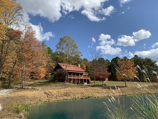 Secluded hilltop log cabin with fishing pond, stunning views, & nature trails