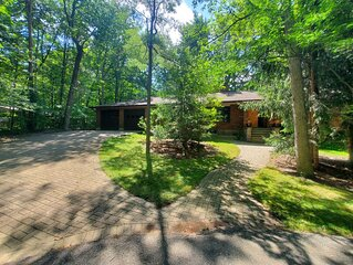 Spacious cottage in the woods steps from private beach in Grand Bend.