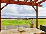 Level lot with expansive lawn and gravel patio with fire pit overlooking beach.