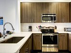 The kitchen has an electric range cooktop, oven, microwave, fridge/freezer