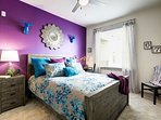 Colorful master bedroom with queen size bed.