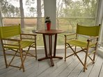 Screened porch with conversational seating and marsh views.