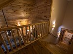 Staircase with double handrails leading to upstairs master bedroom.