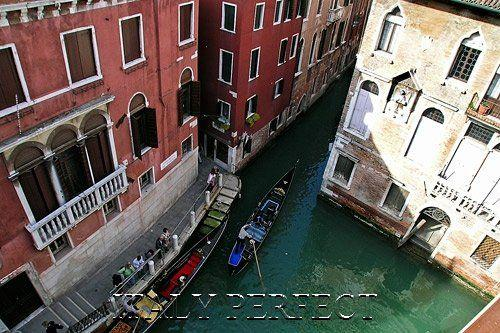 Apartment view of canals and gondolas.