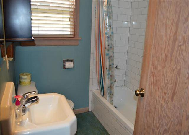 Hall bathroom with tub/shower combo, pedestal sink and stackable washer/dryer.
