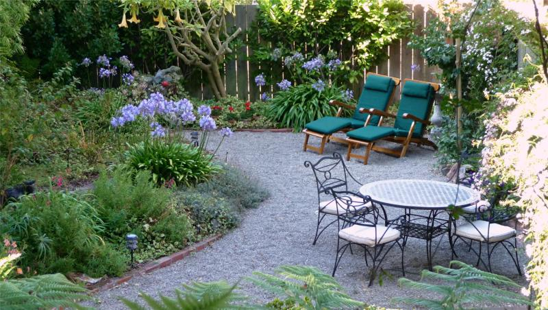 Well Maintained Garden. Wrought Iron Chairs. Teak Deck Chairs. Enjoy Morning Coffee. Relax!