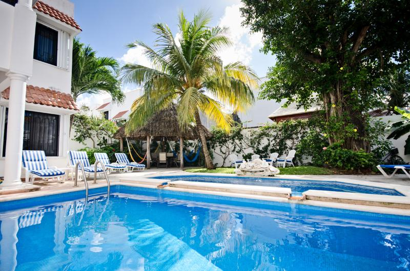 Looking across the pool to the lounge chairs and palapa covered patio