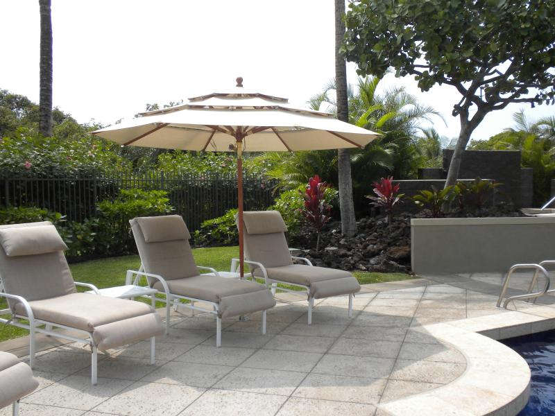Lounges with umbrellas around the pool