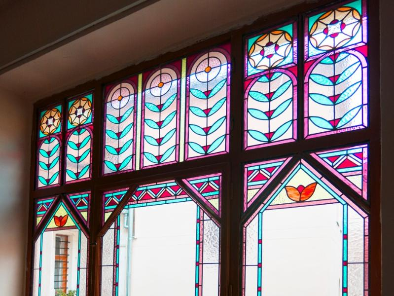 Stained glass window in hall outside apartment door.