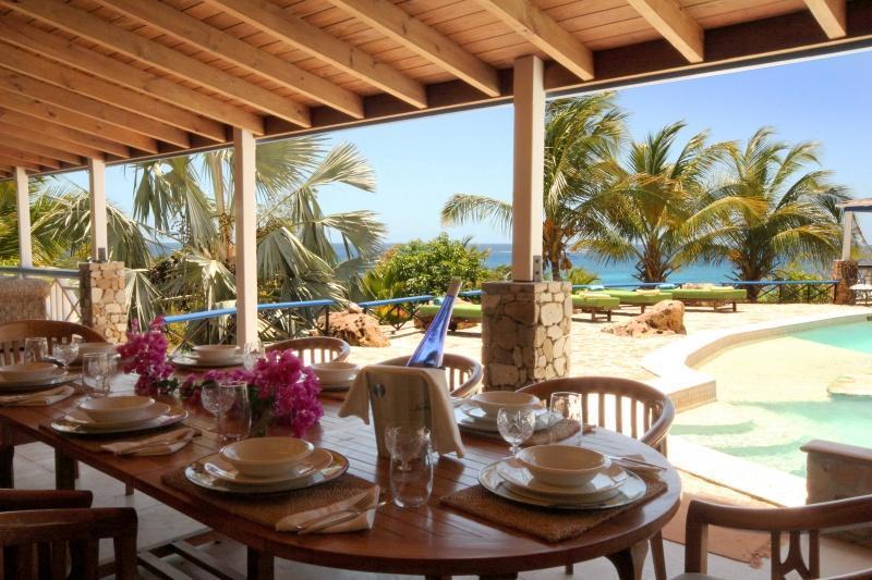Comedor junto a la piscina a la sombra de la terraza amplia
