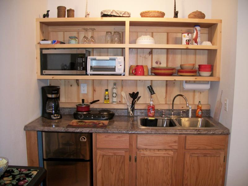 Efficiency kitchen with microwave, convection toaster oven, coffee maker & mini fridge.