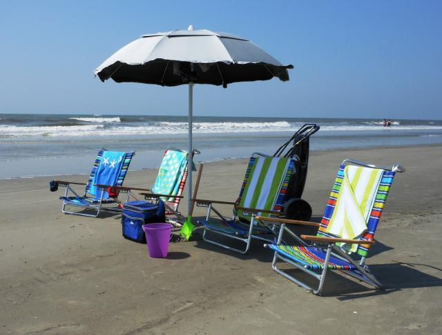 Beach gear provided includes beach chairs, umbrella, cart, coolers, towels, & toys.
