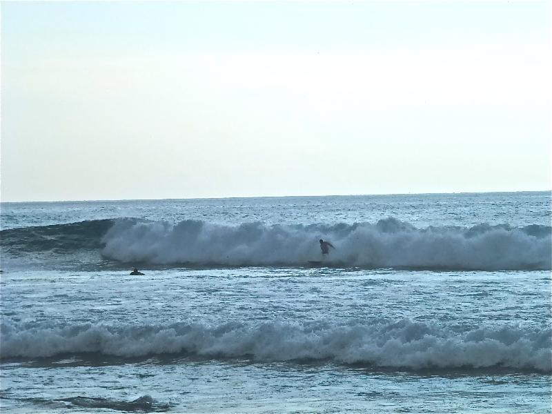 Ver los surfistas en la playa al final de la calle