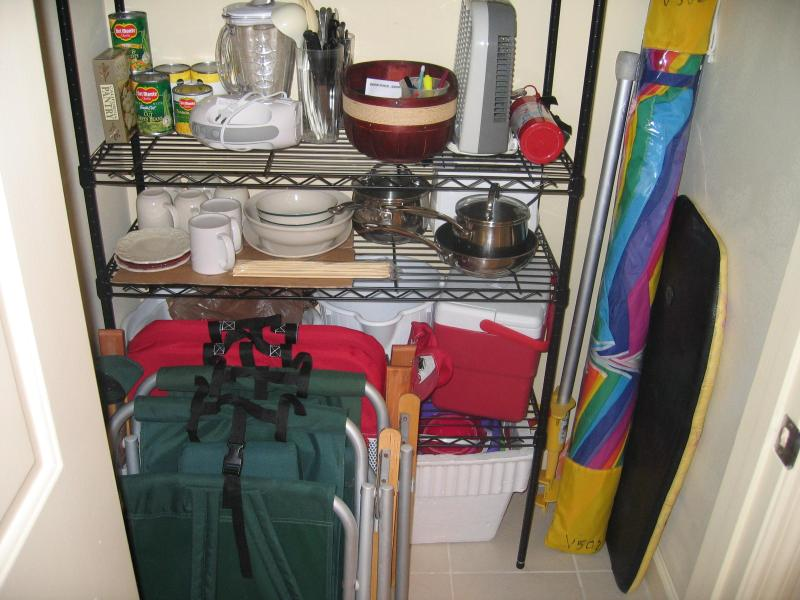 Utility closet showing lightweight but heavy duty beach chairs and beach umbrella and more.