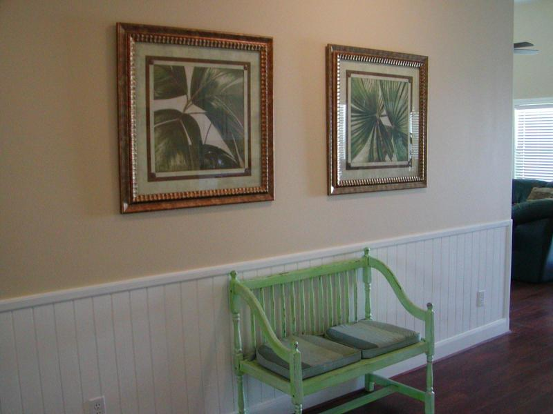 Hall way that leads to master suite and 2nd bedroom downstairs. Coastal decor throughout