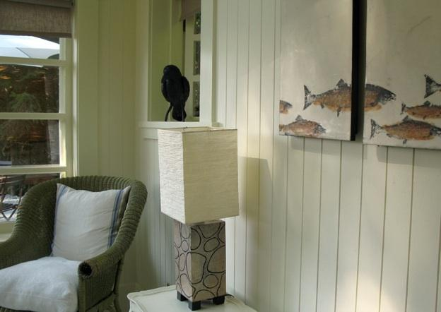 Encaustic salmon paintings and a raven perched on the windowsill