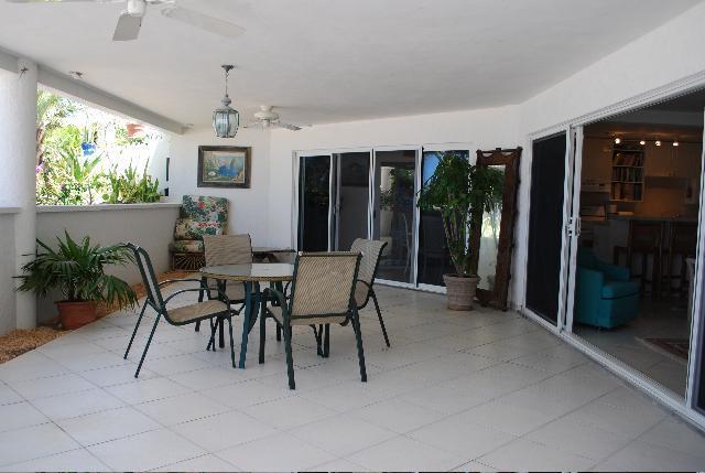 Terraza inferior para el área de dos dormitorios con ducha exterior y Lavapiés junto al mar.