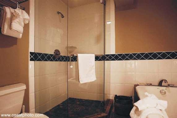 Large main bathroom with, heated floor, a separate glass shower and a bathtub set in slate.