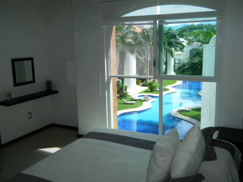 Master bedroom with pool view and mezzanine