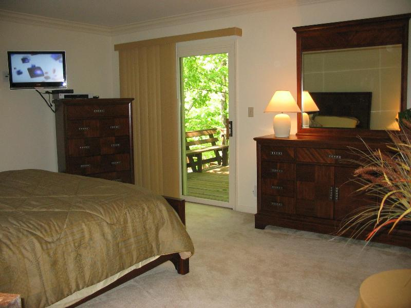 King Master bedroom, main floor, with its own deck, flat screen tv, full bath and vanity area