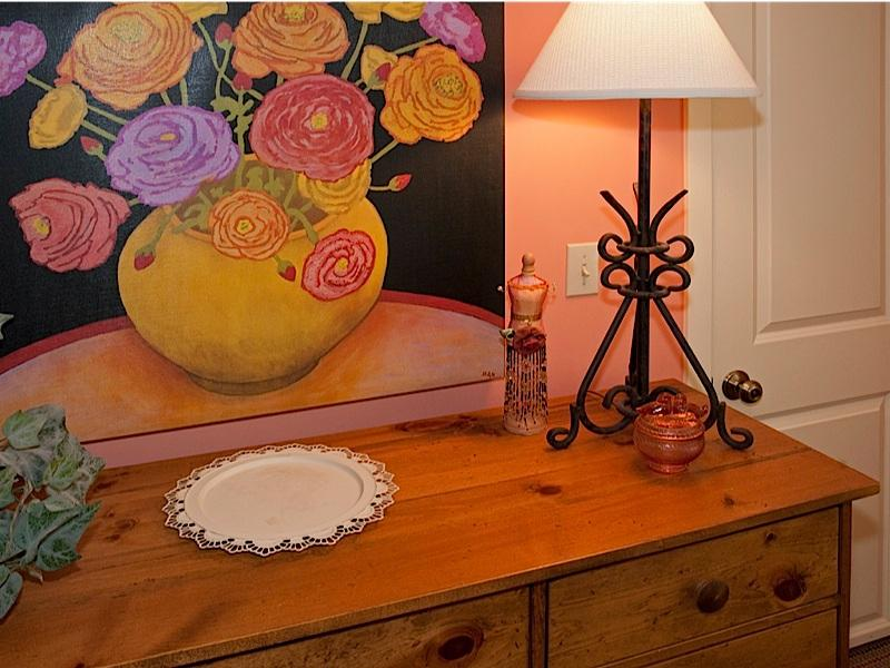 Close up van dressoir, artwork, kleine kast in grote slaapkamer