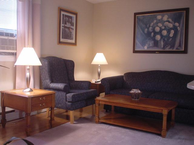 Suite 1. Living Room is Tastefully Decorated with high Wing Back Chairs and Matching Pull Out Sofa.