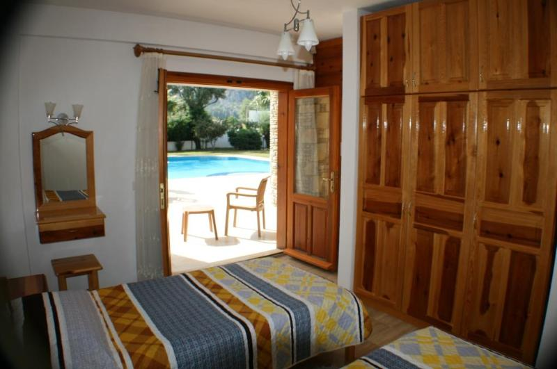 Chambre à deux lits donnant sur patio près de la piscine.