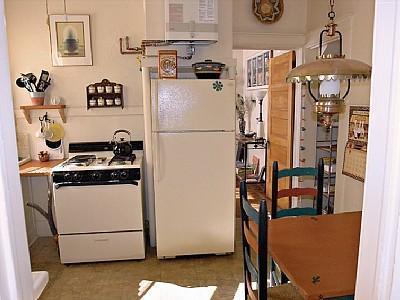 Cucina con elettrodomestici, piccolo tavolo da pranzo. Living Room è in background. Dispensa senza illustrazione.