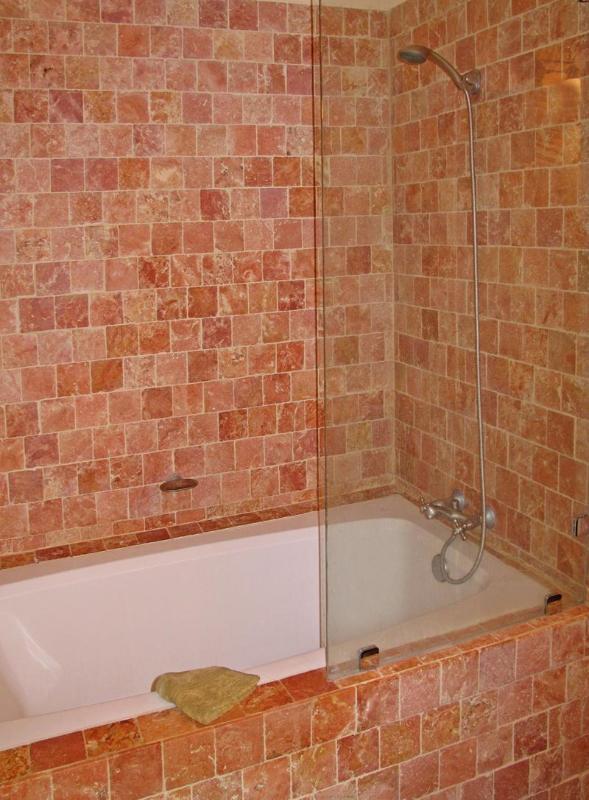 Baño completo y ducha con azulejo de coral en el dormitorio de invitados.