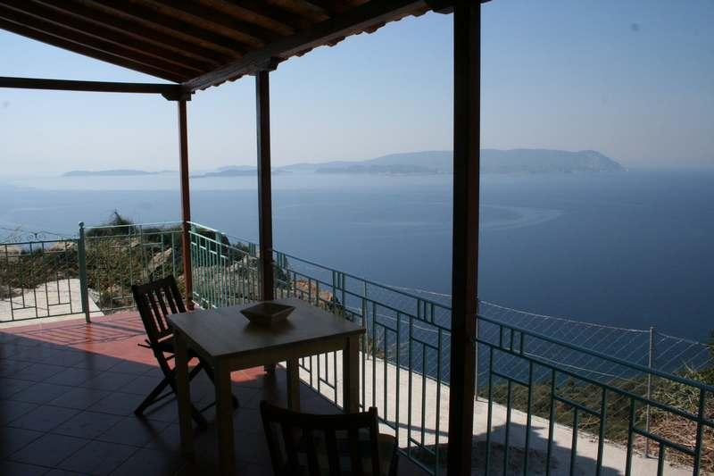Shady balcony with dining table and four chairs with amazing views of Skiathos and sunsets.
