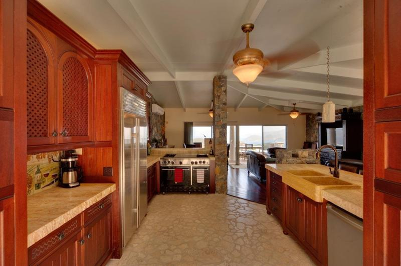 Gourmet Kitchen with Sub Zero refrigerator, Bluestar Range, Travertine slab counters and Coral Stone
