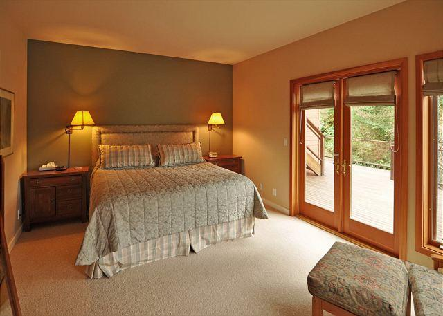 The bedroom features a king size bed and has double doors that walkout to the hot tub.